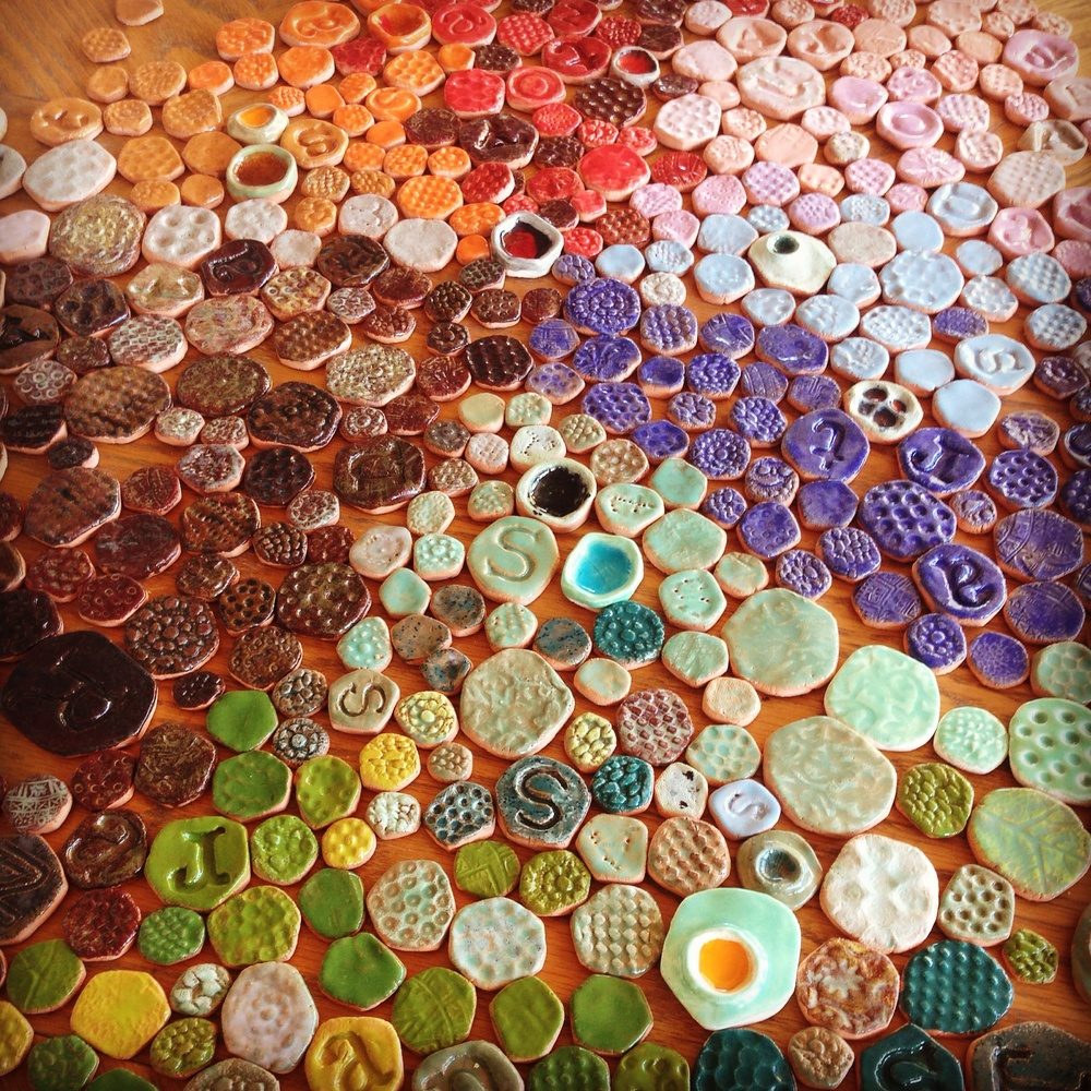 The reality of hand-forming, glazing and firing all of these hundreds of tiles was a bit more than I bargained for. It was a really fun way to experiment with different textures and glazes, though. Some I built into little craters and melted glass in them during the firing process. I carved my own stamps to make most of the letter tiles. I made similar tiles for my Herrudura Tequila project last year.