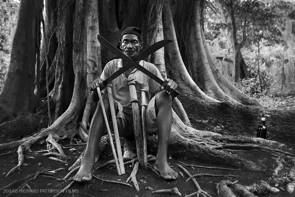 Professor Alred Avril, a master at machete fencing, sits below his family tree in the hills of Jacmel, Haiti.