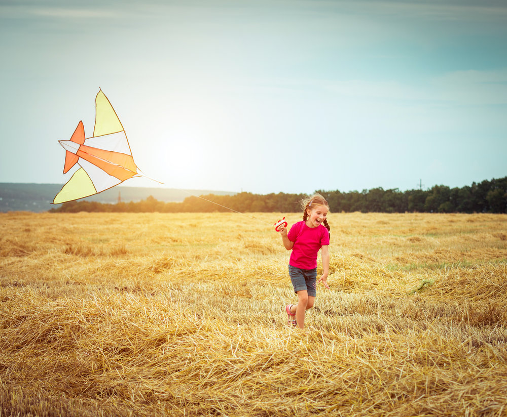 bigstock-happy-little-girl-witha-kite-i-74487529.jpg