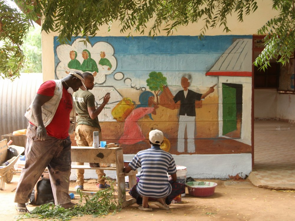 Artists work on mural paintings in Dagahaley Camp, Dadaab