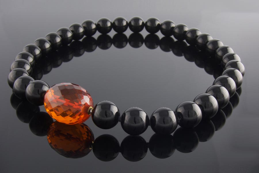 Faceted cherry amber clasp on  black onyx beaded necklace