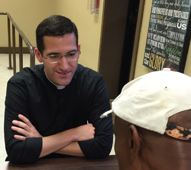 Fr. Patrick visits with one of St. Joseph Diner's patrons.