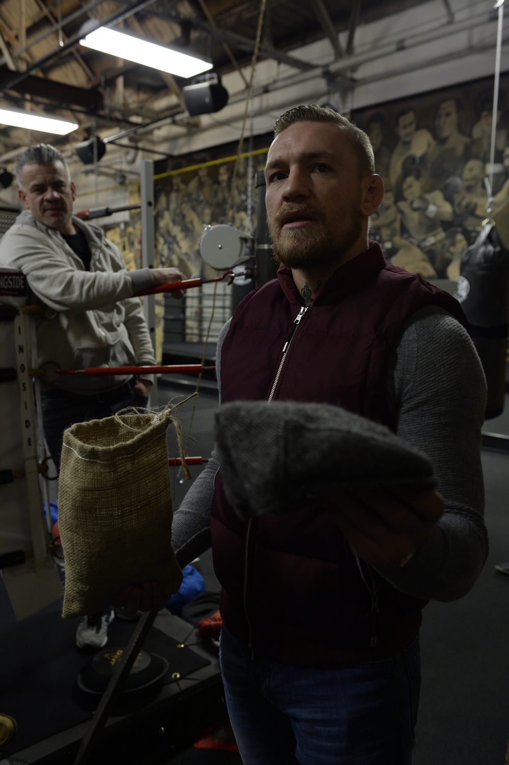 Conor McGregor with the gray heritage cap and burlap cargo bag.  Gym owner Peter Welch observing from the ring.