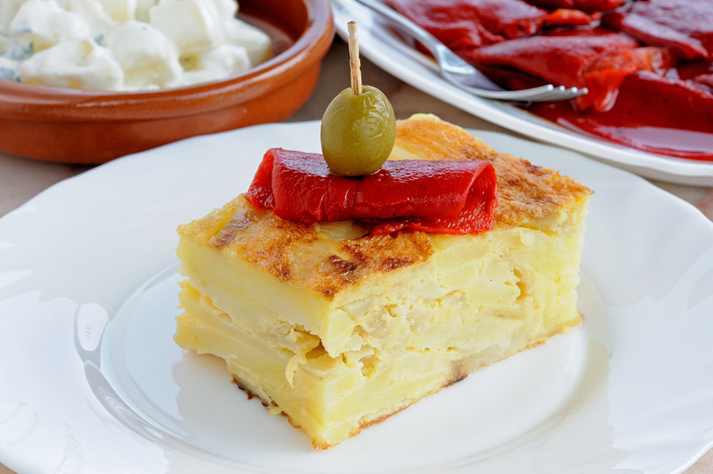 Tortilla española - Irresistible Spanish omelet, made of potato slowly sautéed in olive oil with a combination of vegetables and eggs.