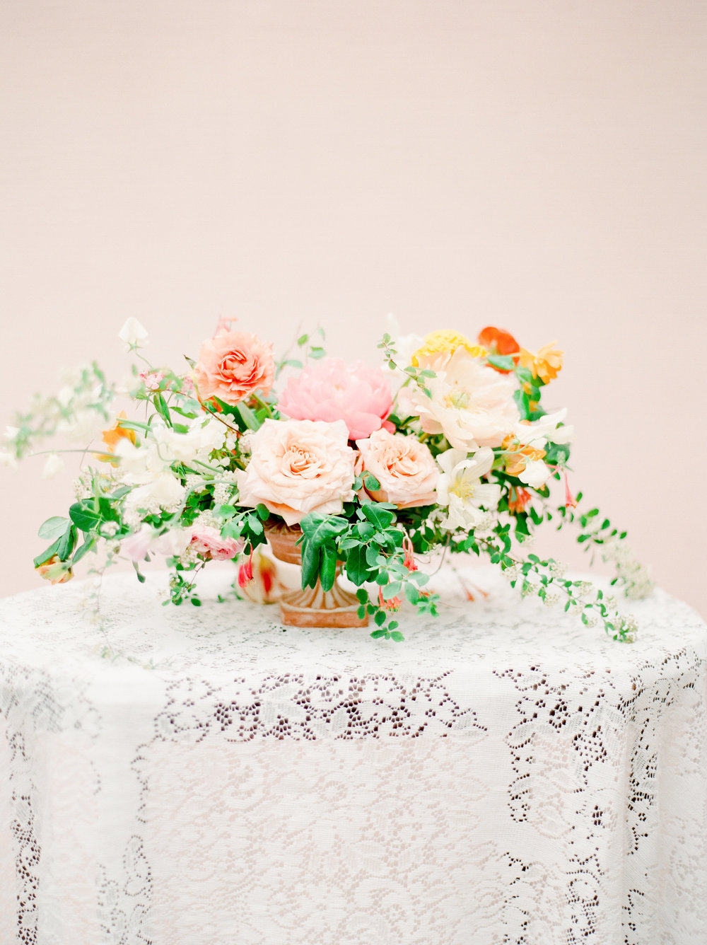A beautiful floral arrangement paired with a lace overlay creates a beautiful welcome vignette at a wedding. Photo by Julie Paisley. Exquisite florals by Petal and Pine. Styling by Feather + Oak.