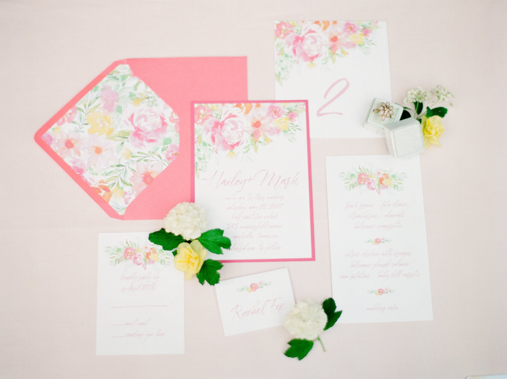 A colorful invitation is delightful to receive through the post while the table elements incorporate more white space to let the tablescape take center stage as a whole. Paper suite by Designs In Paper. Styling by Feather + Oak. Photo by Julie Paisley.
