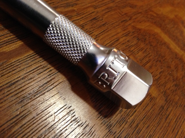 A ratchet extension with a knurled section and a hex fitting for  wrench.