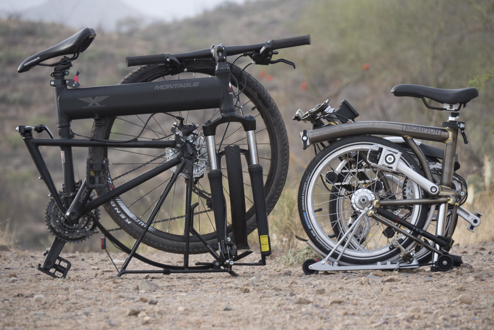 "The Brompton next to an ""ordinary"" (and excellent) folding bicycle, the Montague. The front wheel on the Montague must be removed before folding. The Brompton's wheels fold with it and enclose the drivetrain to prevent you getting dirty while carrying it."