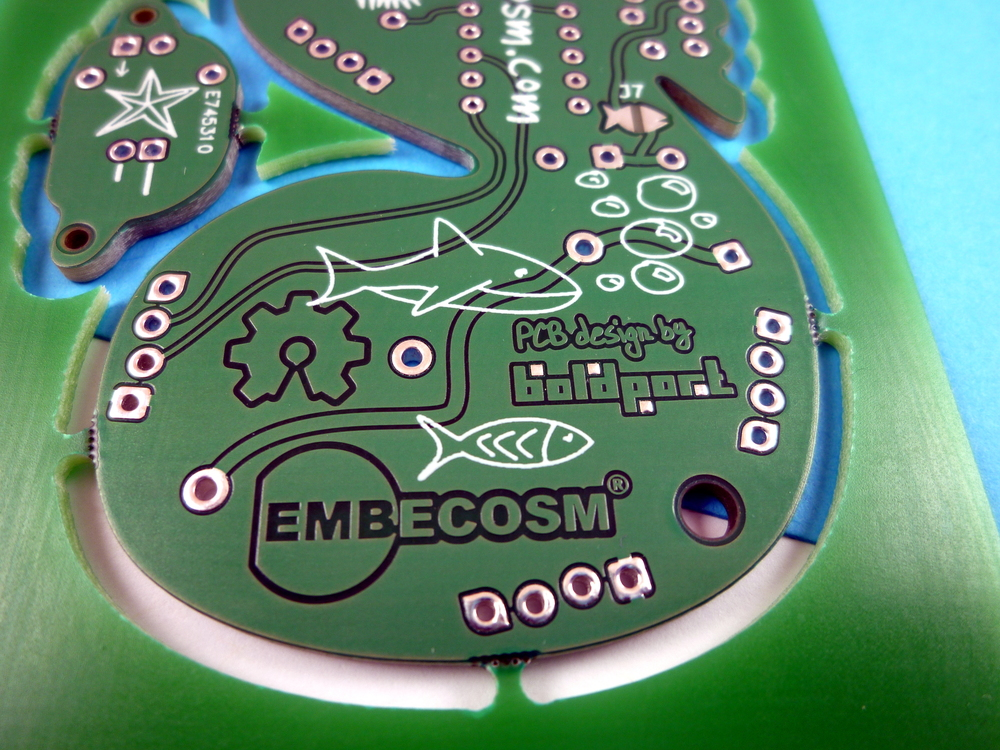 The solder-blob jumper is the on top right; it connects the programmer's 5V to the power plain, and assumes no battery is connected!