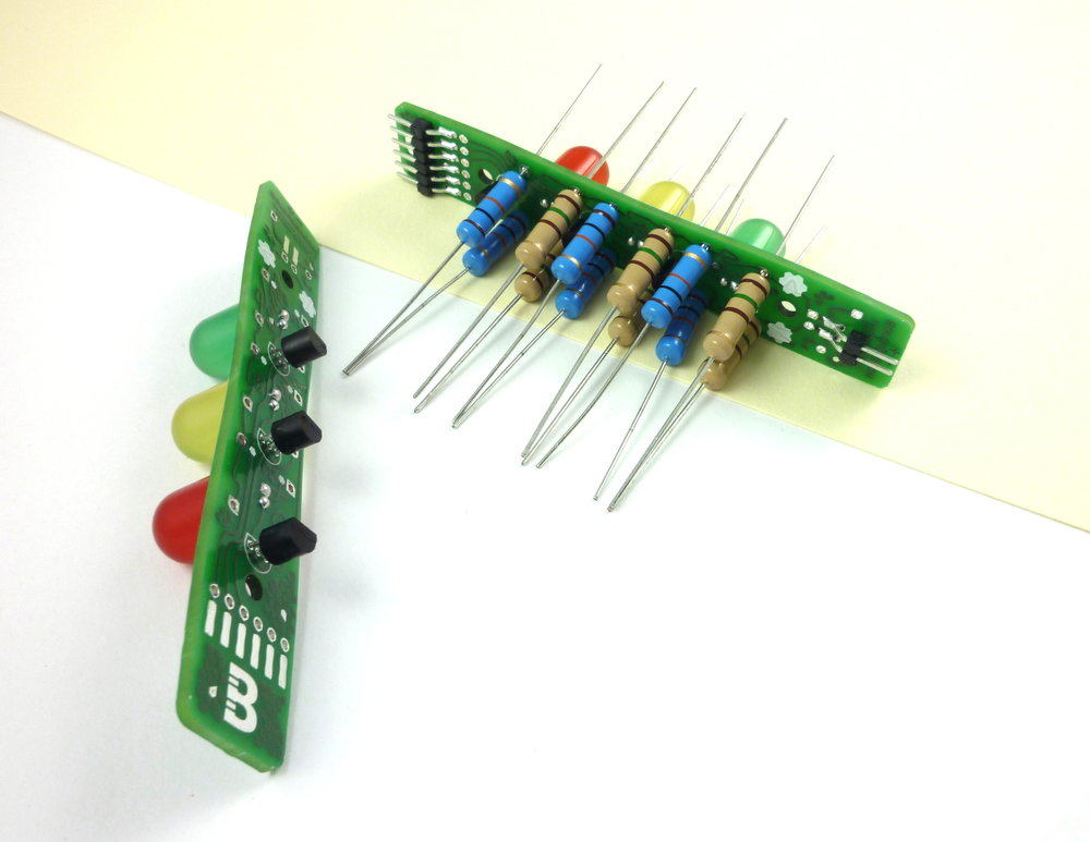 Place the resistors so that they are against the bottom of one of the  boards. Some holes have a gear-shaped mark next to them; that's where  the brown resistors go.