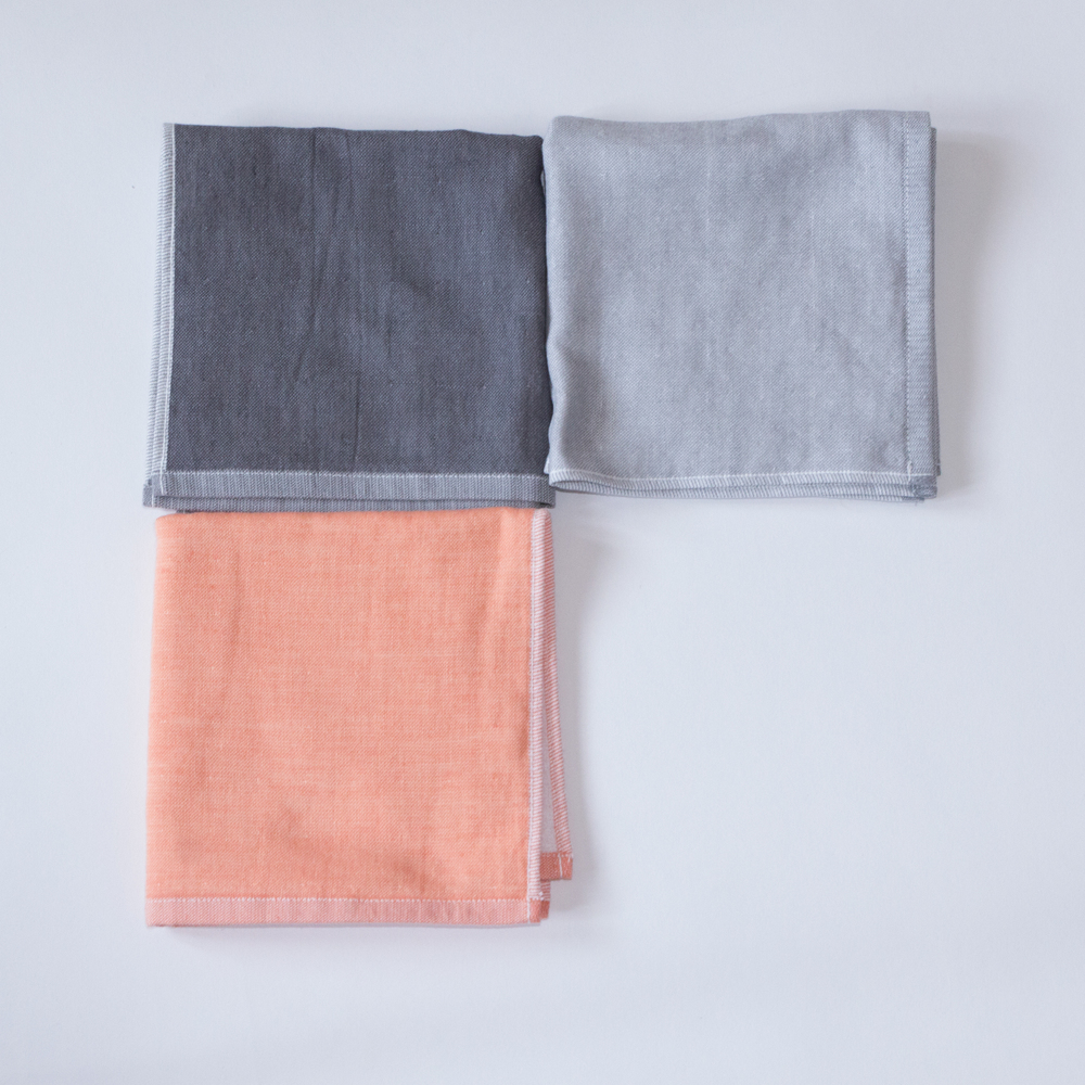 Calm squares of Yoshii two-tone chambray towel in Orange 1, Black 2, and Black 1.