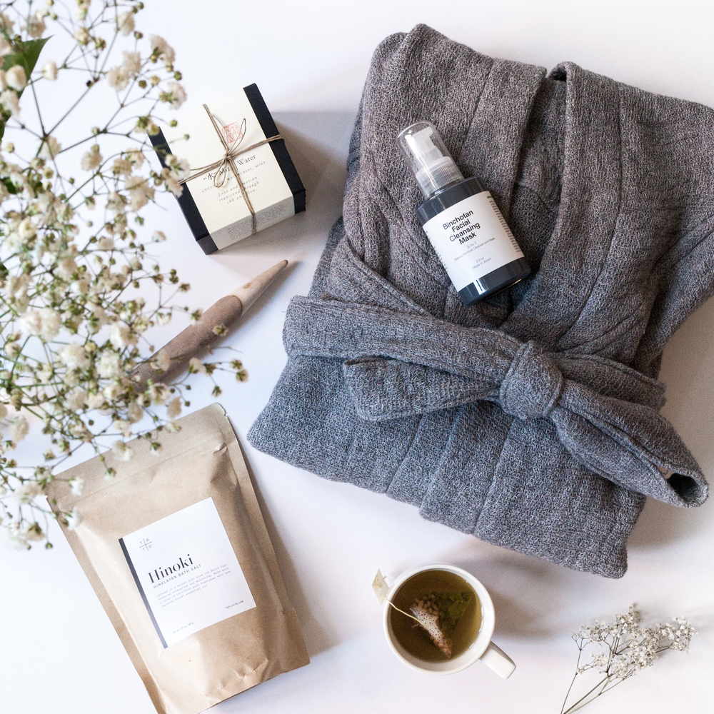 Pictured clockwise from right: Binchotan Facial Cleansing Mask, Lana Bathrobe in Grey, Morihata Organic Genmaicha Tea Bags, Hinoki Himalayan Bath Salts, Shiatsu stick, 5 Elements Candle in Water.