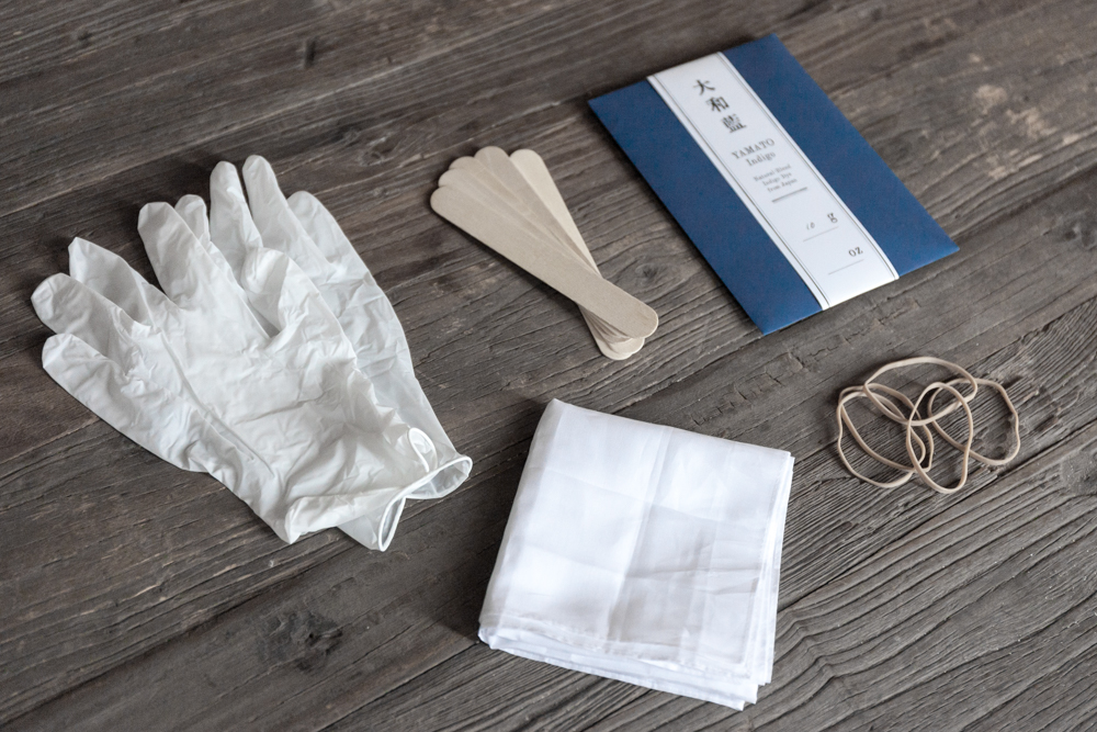 The Yamato Dye Kit has everything you need for basic natural indigo dyeing:  10g of indigo dye, wooden sticks, rubber bands,  a pair of latex gloves, and three white cotton bandanas.