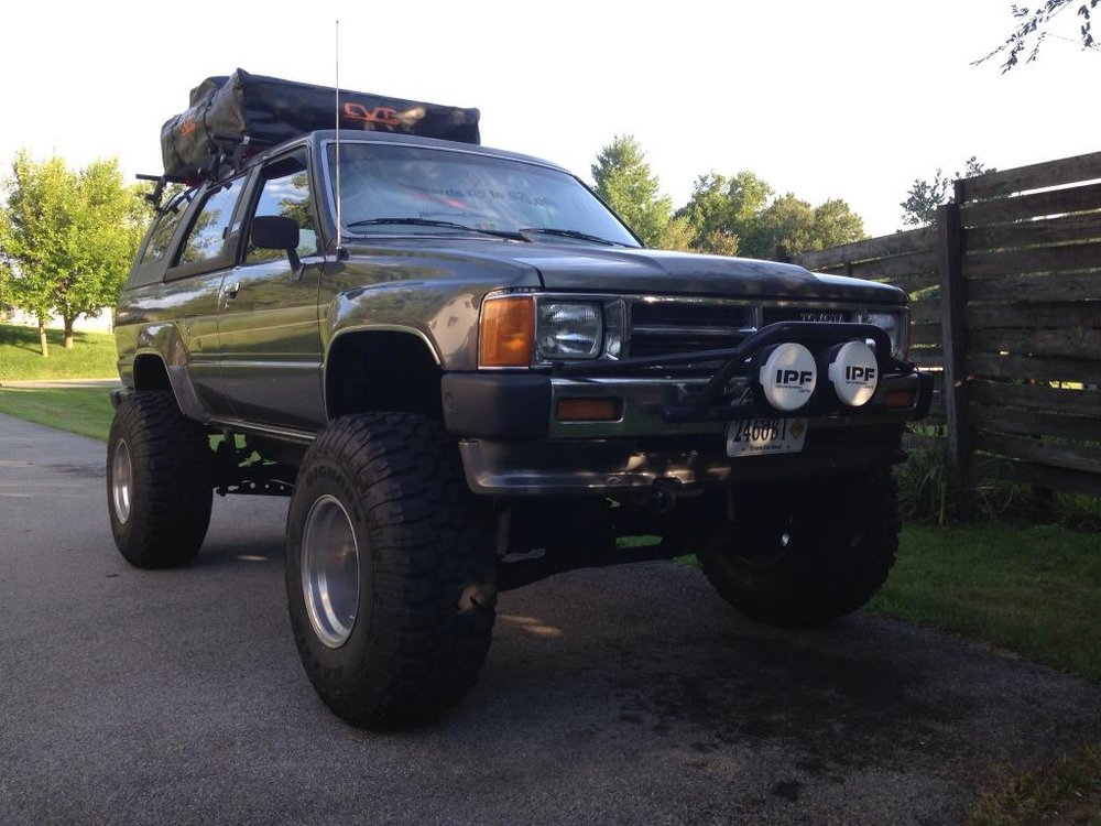 """1986 4Runner 22re SR5. Transformed from a molded driveway ornament to the beginning of many overland adventures. The owner installed a 4.5"""" lift, with a custom truss, 35"""" Maxxis bighorns on 12"""" Alcoa wheels. The 22re has had an RV cam, flamethrower injectors, and performance header installed. The CVT rooftop tent and annex along with the rear of the Runner will accommodate 6 adults. This truck is a blast from the past with a perspective on the future. Erik Hinchey • 1986 Toyota 4Runner"""