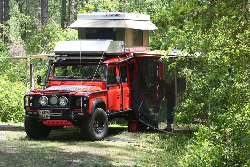 The new and improved evolution of our worldwide expedition rig. This vehicle is equipped with a Bundutec electrically operated roof top raising tent that can be entered into from the floor inside the truck or from a ladder externally. She is equipped with 160 watt solar panel system that feeds all our electrical needs and all lighting is LED. She carries up to 50 gallons of diesel and 30 gallons of fresh water which can also feed the engine heated external shower which is temp regulated. Mechanicals are a TD5 engine with upgraded VNT turbo and performance allisport intercooler with Mastaz performance ECU. Trans is stock r380 with GKN electric overdrive, diffs are ARB air lockers driven by GBR heavy duty driveshafts. 12k lb front mounted husky superwinch and rear mounted 8k lb winch. All 6 wheels fitted with Coyote internal Beadlocks. Suspension is Old Man emu springs and fox racing remote reservoir shocks and Overtyme engineering castor corrected susp ension arms. Exterior protection and security is by a LRC custom built exocage who also supplied the custom extreme protection front bash plate. Interior comfort is supplied by custom recaro front seats and custom rear convertible storage/seating system, all kept toasty warm by webasto heating systems.. No a/c...we sweat like real men.. External decals are reflective for added visibility. Vehicle is equipped with multiple anti-theft devices and remote tracking that can shut down the vehicle from anywhere in the world.