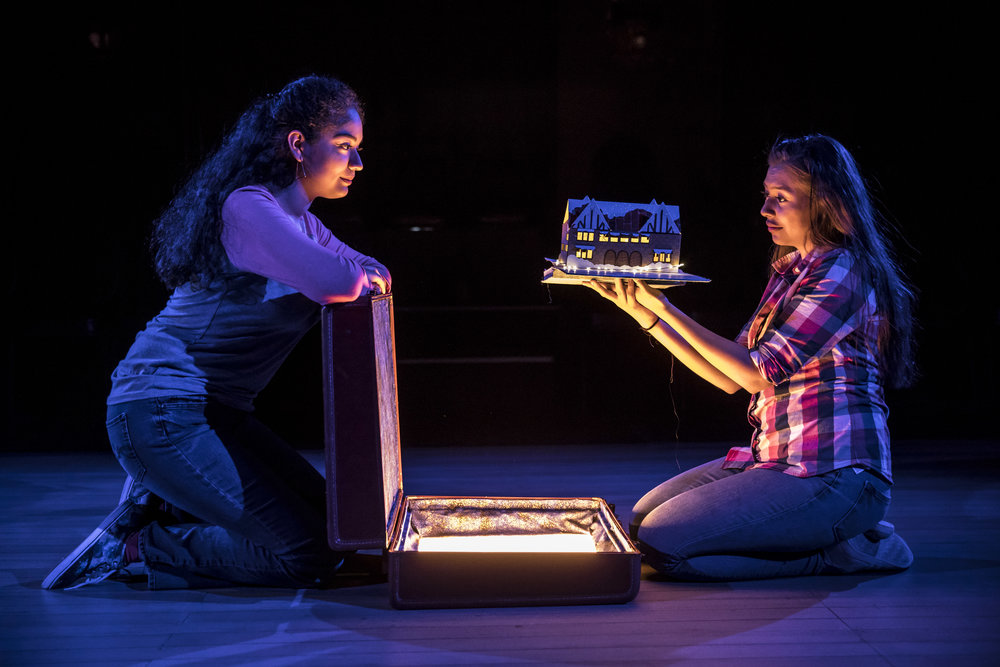 Daniela (Jennifer Calderon) pulls a pop-up book of the Albany Park Theater Project building out of a magic suitcase, while her past self (Mariana Rosas) looks on.