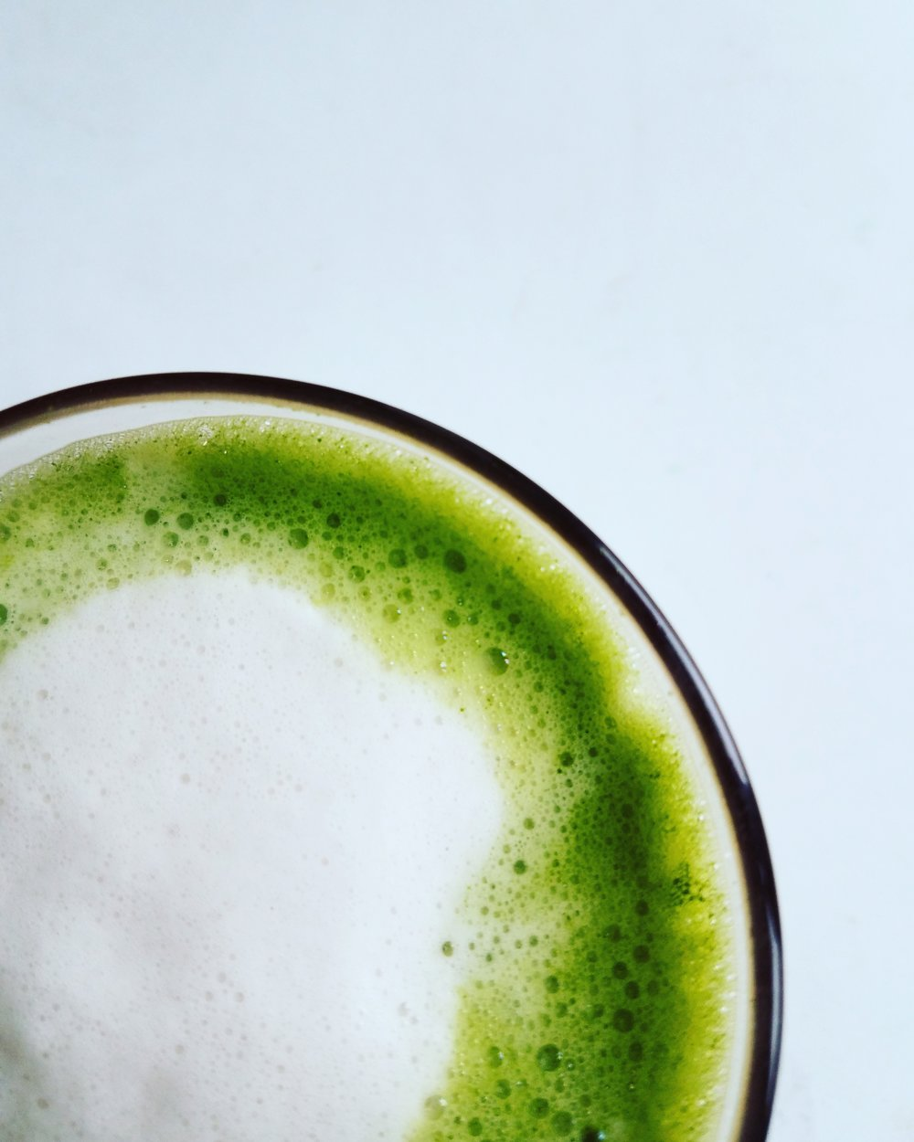"Matcha is delicious. REALLY delicious. It is creamy and velvety and DELICIOUS. Not only that, it is AMAZING for you. It is said to boost your metabolism, enhance weight loss, detoxify your body and prevent premature aging. Research is even being carried out into its  anti-cancer benefits . Oh, and it's delicious. Go get a cup RIGHT NOW and read on about this magical powder. Here is my little love letter to Matcha.   What is Matcha?  Matcha comes from the same plant that all true teas come from; Camellia Sinensis. The leaves from this plant can be made into green tea (unfermented - simply steamed and dried), into oolong (partially fermented) and black tea (fully fermented). Matcha is a true green tea, but growth style, harvest and production are different.  This plant does have different varieties, some of which produce higher grade Matcha, the best coming from Samidori, Okumidori and Yabukita.   Why is Matcha so bright?  Three weeks before harvest the tea plants are covered with bamboo mats or tarp, depriving them of sunlight. This increases the chlorophyll content and turns the leaves a dark green which gives Matcha it's color. The leaves are then harvested, steamed and air-dried. They are then sorted for grade, destemmed and deveined. It is at this point that the leaves become ""tencha"". Once the tencha is ground it becomes Matcha.   What grade of Matcha should I choose?  If you want to reap the full health benefits of Matcha, look for ceremonial grade or hyper-premium. These best grades are ground on a stone mill. This process is slow, keeping the temperatures low to preserve high nutrient levels. It also produces a molecule with a specific shape which influences the taste and feel of the Matcha. Lower grade Matcha, such as culinary-grade, is ground by machines and can taste bitter when made into a tea. When buying Matcha, look for the uber-vibrant green color provided by the overproduction of chlorophyll. If it is duller (like moss), don't expect best quality.   What does it taste like?  Matcha has an umami taste (a Japanese term for the fifth scientific taste meaning ""rounded, rich, savory""). It tastes quite different from other teas. I was never a big fan of steeped green tea, but I love Matcha.   Why should I try Matcha?  Matcha has a different effect on your body than coffee. The caffeine from Matcha delivers a calm energy rather than an urgent, jittery restlessness. Matcha has long been used by Buddhist monks to help their daily meditation due to the combination of caffeine (which fights off drowsiness) and L-theanine (which sharpens focus and concentration).  L-theanine, present in Matcha at around 5 times the levels when compared to a regular cup of green tea, is an amino acid which is reported to have a calming, relaxing effect, reducing anxiety. Whilst espresso delivers an instant effect, the l-theanine in Matcha is released slowly, keeping your energy levels up longer.     What else can Matcha do for me?  Matcha is rich in epigallocatechin gallate (EGCG, also known as catechin). Because you are taking the whole leaf, instead of just steeping and throwing them away, one cup of Matcha can deliver the health benefits equivalent to 10 - 20 cups of regular green tea. EGCG is said to prevent cell degeneration and premature aging. It can boost your metabolism, assisting your body's ability to utilize energy.   How to make a great cup  ·      Source the best quality possible, making sure it is from a Japanese farm. ·      Place a small amount, around 1 teaspoon, Matcha into a cup or bowl. ·      The water you add should be hot but not boiling - between 150 and 170 degrees. If you don't have a thermometer, after boiling the kettle, remove the lid and let it stand for a minute or two before using. ·    Add a small amount (a few tablespoons) of this water to the cup, whisking into a soft paste, adding more as you whisk to reach the consistency you desire. The ratio of Matcha to water is up to you - the more Matcha the thicker and frothier the tea. You can use the traditional chasen (a bamboo whisk) or an electric milk frother wand but if you don't have either, begin by using a teaspoon and mix in the same way as you would cocoa powder, ie small amounts of liquid until a paste is formed, adding a little more at a time. For a teaspoon of Matcha I would suggest a cup around the size of a macchiato (longer than an espresso, shorter than a (true!) cappuccino). ·      If you like, replace some of the water with a small amount of foamed milk. I use ⅔ water ⅓  unsweetened almond milk . ·      If you really need, add a drop or two of (best quality!) stevia. I did this in the beginning but now prefer the taste without. ·      Matcha is also delicious served iced.  If you haven't tried Matcha yet, please don't let your first experience be from any old cafe. Do it yourself or search out somewhere that serves the best quality. I have experienced some terrible versions out there, often low quality, overly sweetened or just drowned in a store-bought milk which takes over the taste. Of course, this isn't true of all cafes, there are a few who serve a truly good version. If you make it for yourself at home, try it the traditional way, with only water, and then if you like, add a little steamed (non-dairy is best)  milk  and (best quality) sweetener only if you need it."
