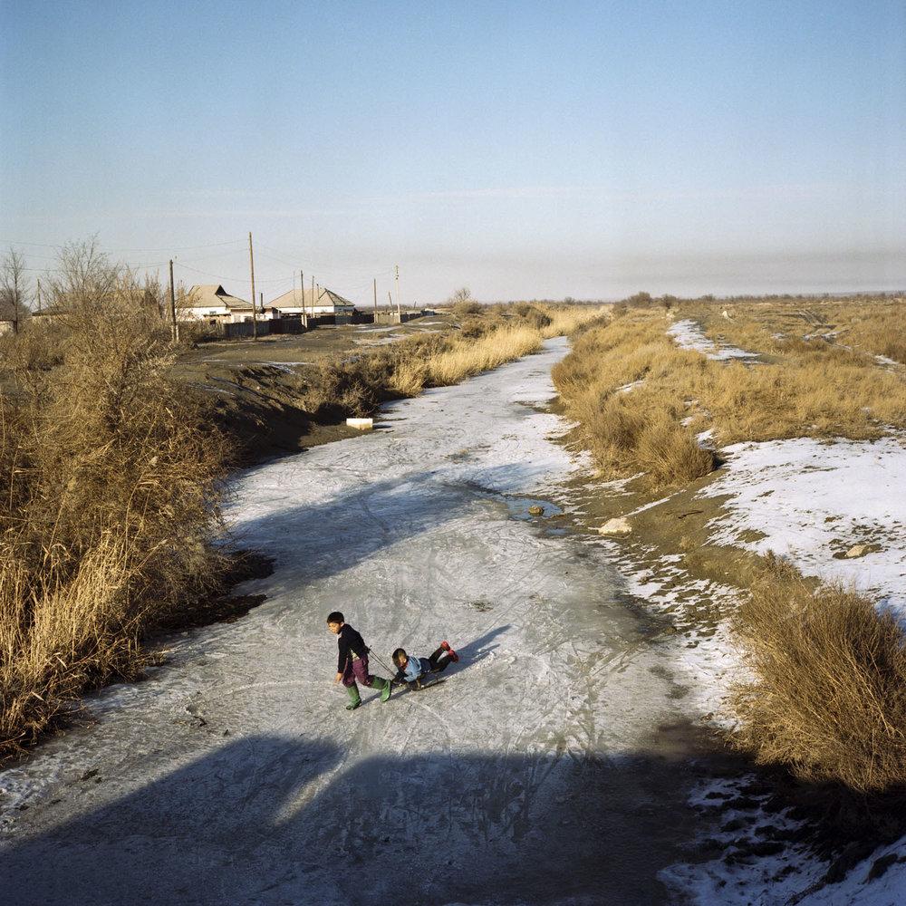 Kazakh children playing on a frozen river in Ushtobe, the first place Koreans were deported to in 1937. Ushtobe, Kazakhstan. December 2014.