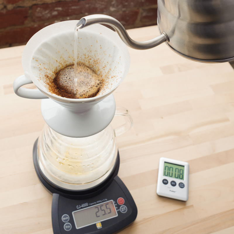 4. Pouring in a circular motion, slowly and gently add 40g of water over coffee bed. Take care to not pour on edge of coffee bed and filter.