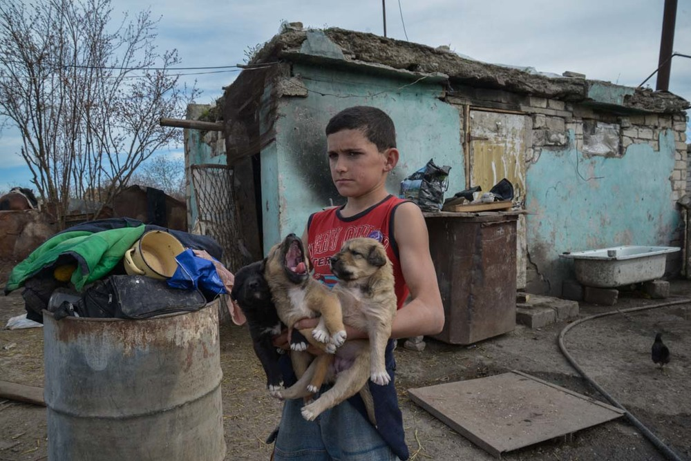 Arkadi, 14, holds young puppies in his farmyard in the ghost town of Agdam, north-east Nagorno-Karabakh. During the war, the town was used by Azerbaijani forces to bomb the capital Stepanakert. It was captured by Armenian separatist forces and almost completely destroyed during an offensive in 1993 to prevent its recapture by Azerbaijan. Due to its proximity to the front line, only a few farmers and their families live in Agdam today.
