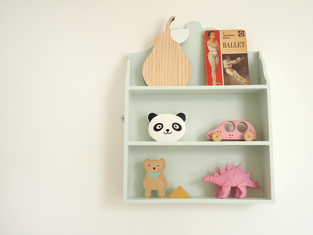 Wooden pear , £10, LaLa Loves Decor; Ballet book, car boot sale find, Panda money box, vintage shop find; painted car, gift from grandparents;  Wooden bear & triangle (part of a set) , £42, desEnfantillages,  Dinosaur light , £11, Sarah and Bendrix