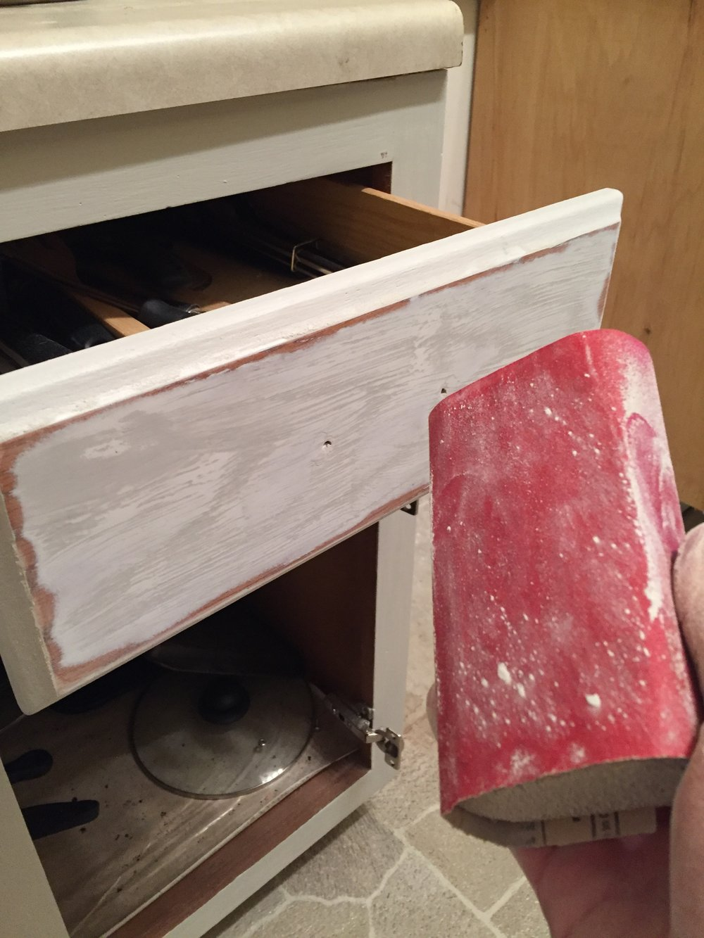 Sanding after the first coats of primer and color have been added.  The drawers didn't feel smooth enough, so we went to town on them.  You can see the highs and lows in this progress pic.