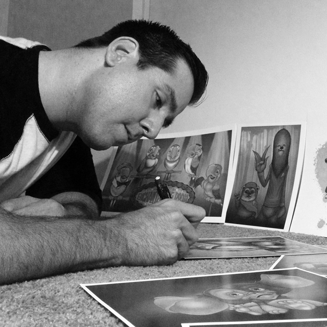 Rey Paez signing his artwork.