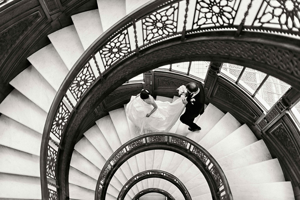 A bride and groom walking down a spiral staircase.