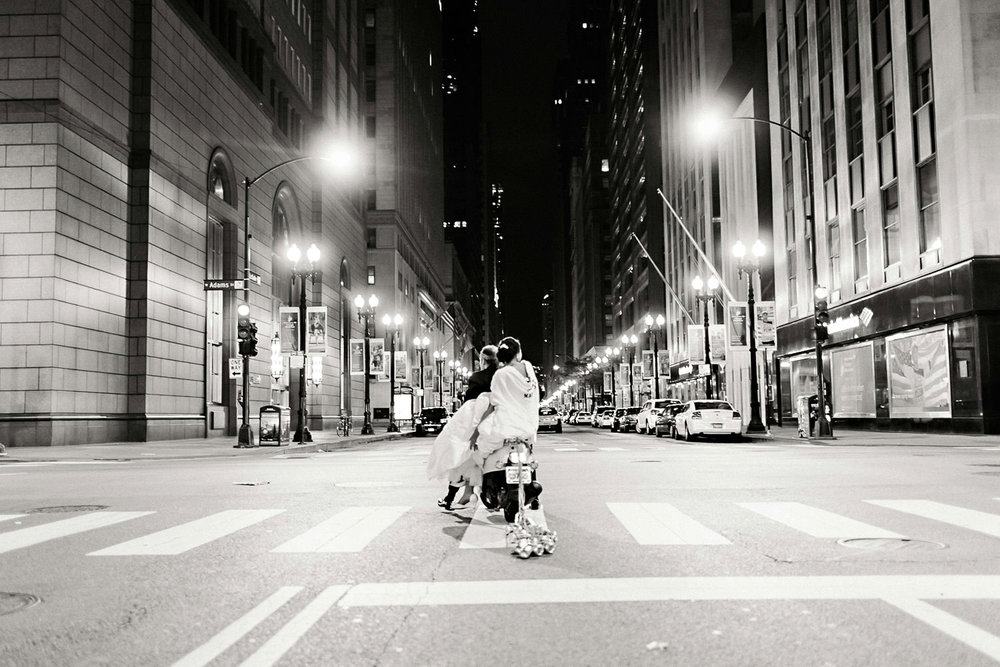 A bride and groom's Chicago sparkler exit on a scooter.