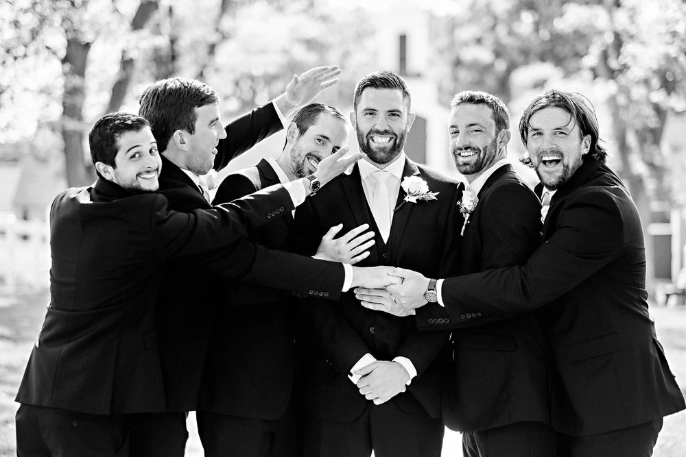 Groomsmen joke with the groom during bridal party photos.