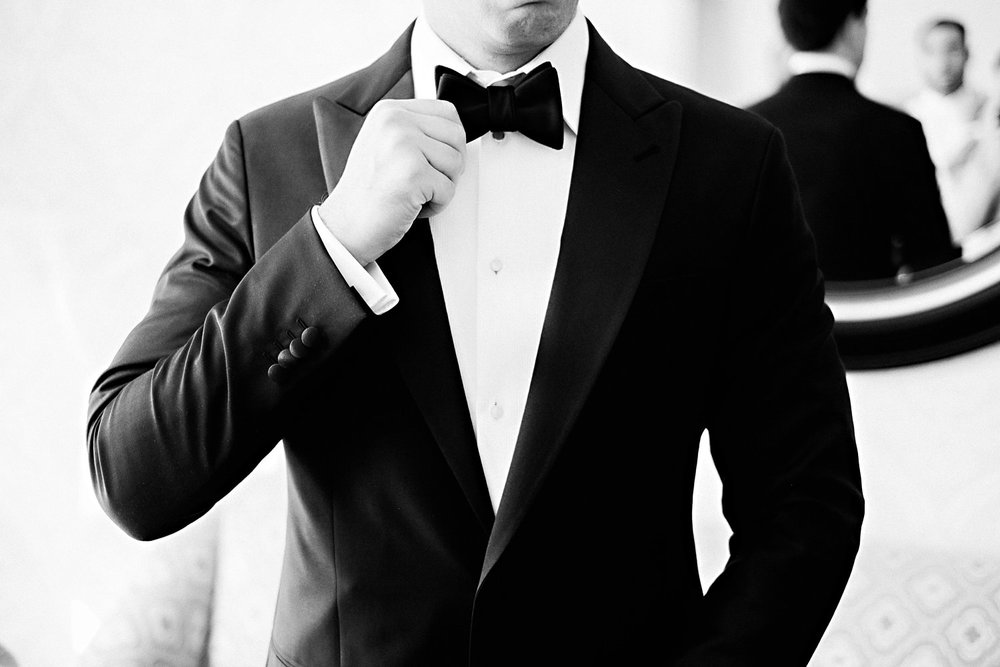A groom adjust his bowtie.
