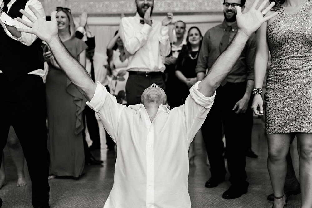 A groom dances at the reception