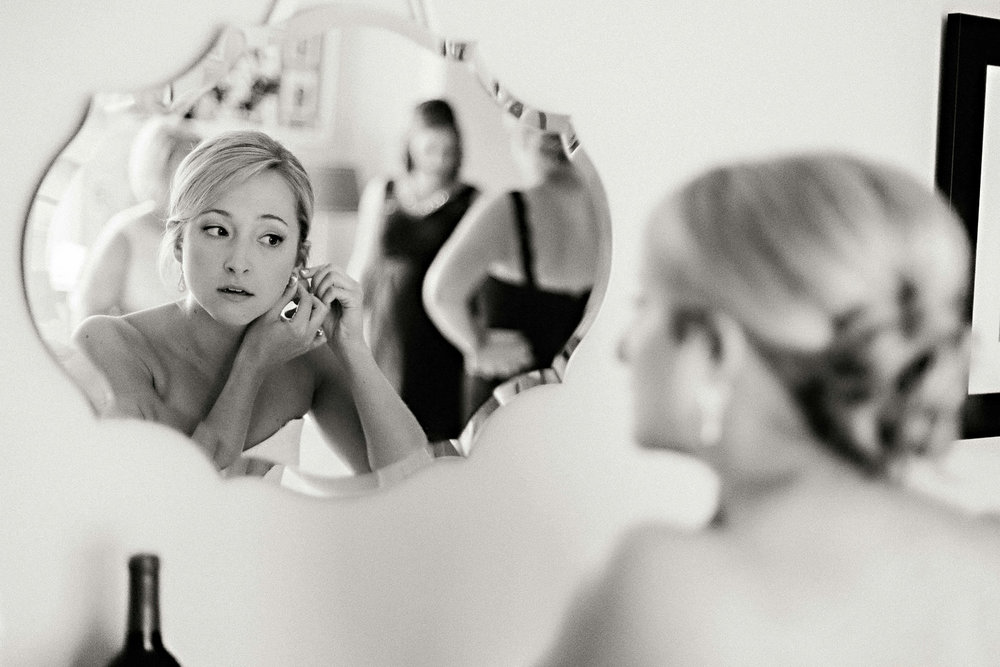 A bride puts on her earrings in the mirror.