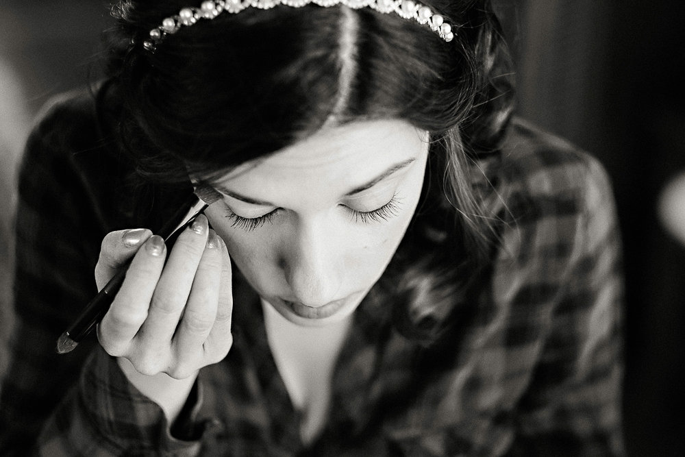 A bride finishes her make up.