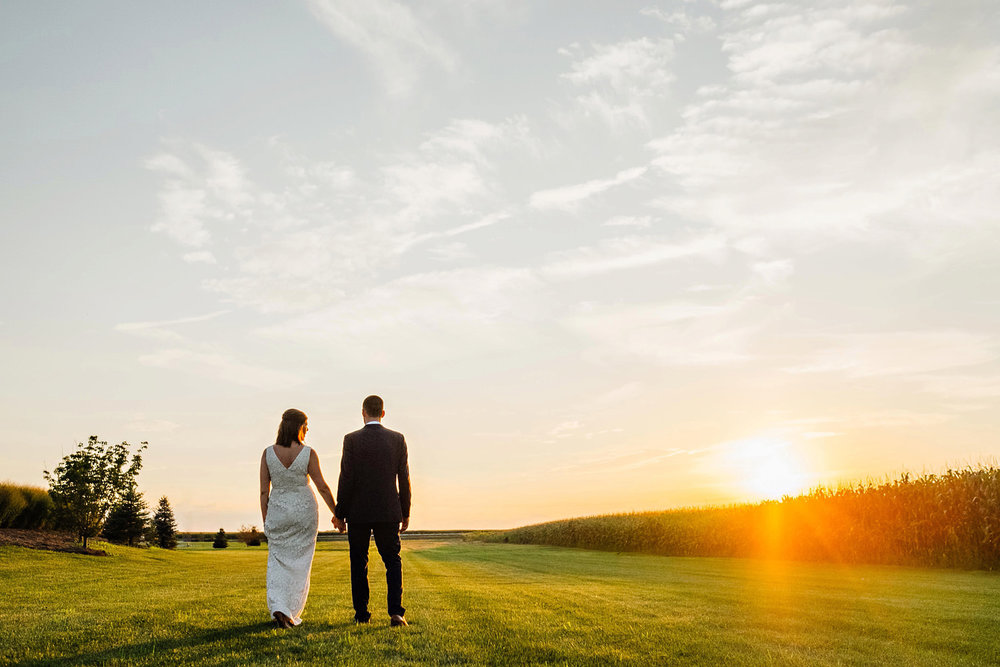 Bride and groom walk in the light of the sunset