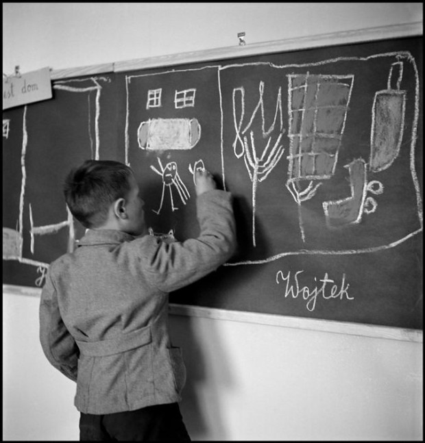 "Poland, Warsaw, 1948. ""In a school for mentally disturbed children, one of them, Wojtek, draws his home on a blackboard"" by David Seymour."