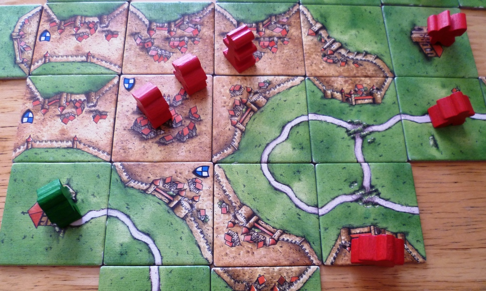 Carcassonne Mid-game with red laying claim to a massive town