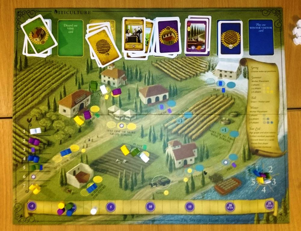 "The Viticulture main board, mid-game.   The ""Summer"" side is on the left and ""Winter"" on the right - we're in Summer right now, and players have been planting vines, building structure, using their Summer visitors, and various other actions.   You can also see the card stacks at the top, (L to R:  Vines, Summer visitors, Wine orders, Winter visitors)."