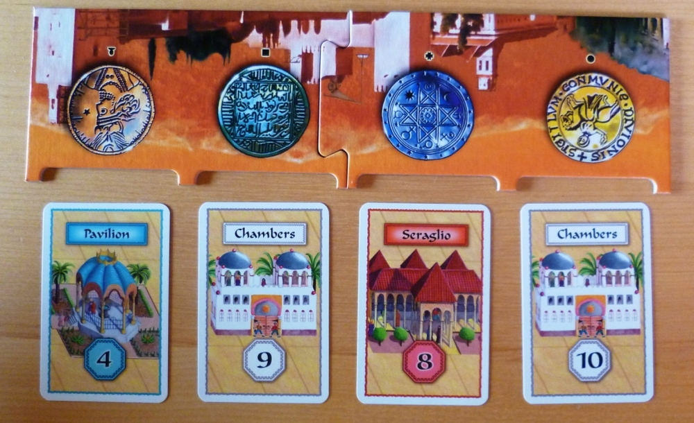 The board shows the currencies, the cards are the buildings, e.g. the White building on the right needs at least 10 yellow to purchase it.