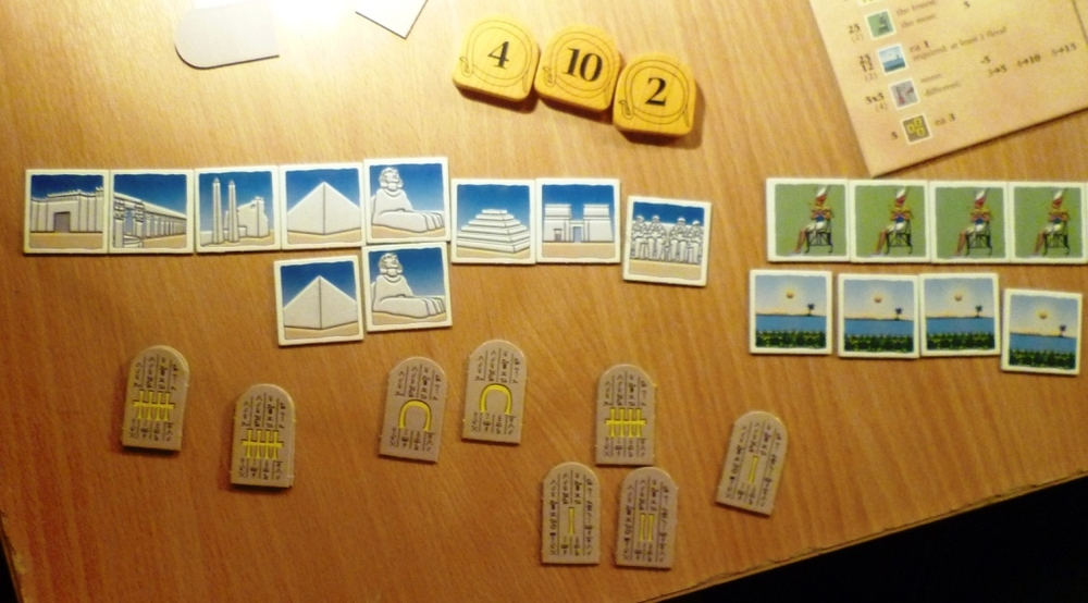 This player has bidding tiles 2, 4 and 10 and has collected quite a few monument tiles for scoring at the end of the game.