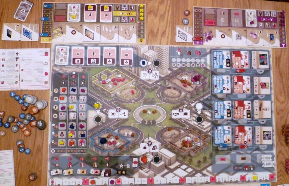 Overhead shot of the main board, the 4 main pawn positions and the associated actions are North South East and west of the central plaza, 2 of these spaces are occupied by Red (S) and Yellow (W).