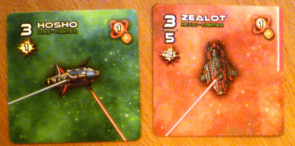 Two of the cards in Stellar Conflict - the lasers show the direction the elastic bands are stretched.