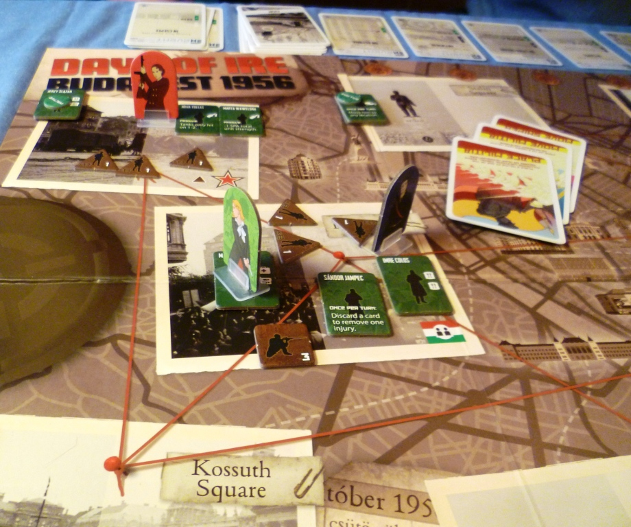 The photos on the board are locations in Budapest, the red lines depict routes, the standees are the revolutionary players, green are revolutionist characters and the brown pieces are SPA forces.