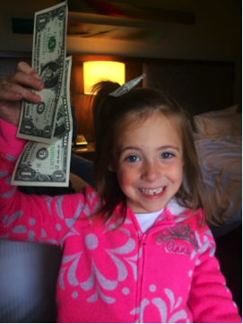 Smiling girl holding up a pair of one dollar bills.