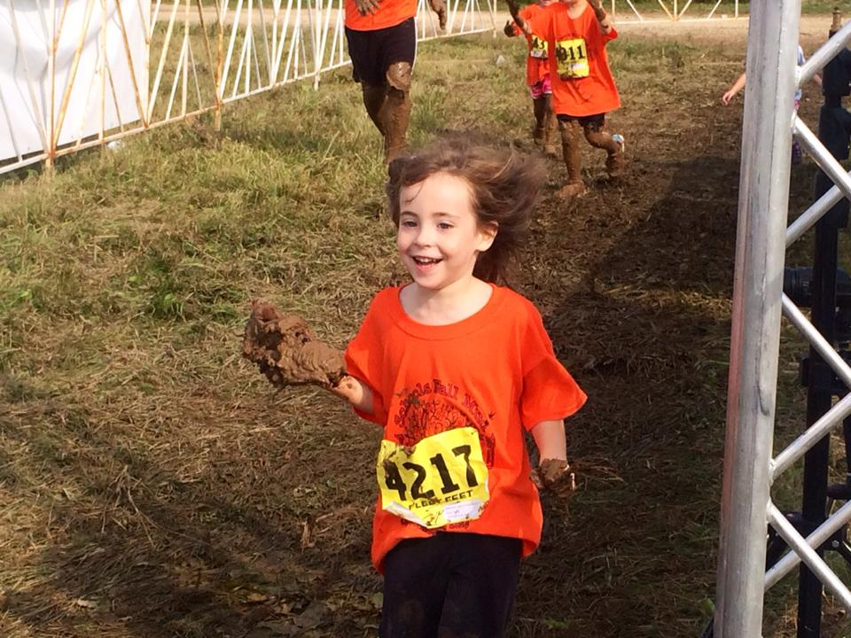 Aubree, Dr. Kaveh's, daughter crossing the finish line with a muddy shoe in hand but all smiles!
