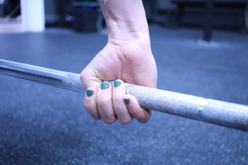 Hook Grip   The hook grip is what we use for the Olympic lifts and their variations (the snatch and clean and jerk). These lifts require you to move the bar fast. The hook grip allows for a secure grip even with high bar speed. This grip involves placing your thumb under your other fingers instead of wrapping it around the bar. The first two (or three) fingers thus hold the thumb and the barbell at the same time.  The hook grip can be challenging or uncomfortable for new athletes, however, it is worth it. Like anything, it gets better with practice, so if you find it uncomfortable, try it out with lighter weights first or by hanging from a pull-up bar to get used to the feeling of pressure on your thumbs.