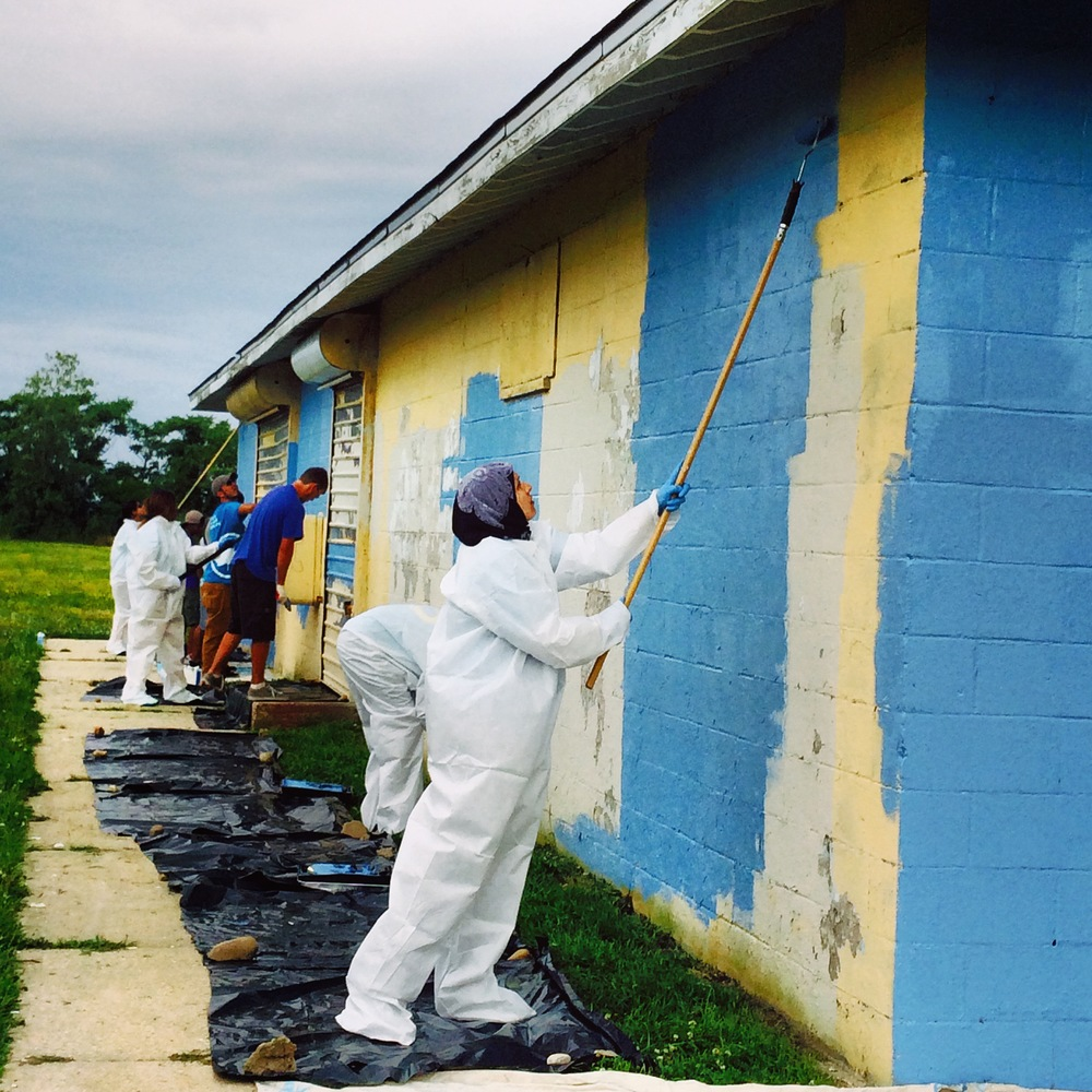 Volunteers spruce up a building with a fresh coat of paint at American Ballfields Park.
