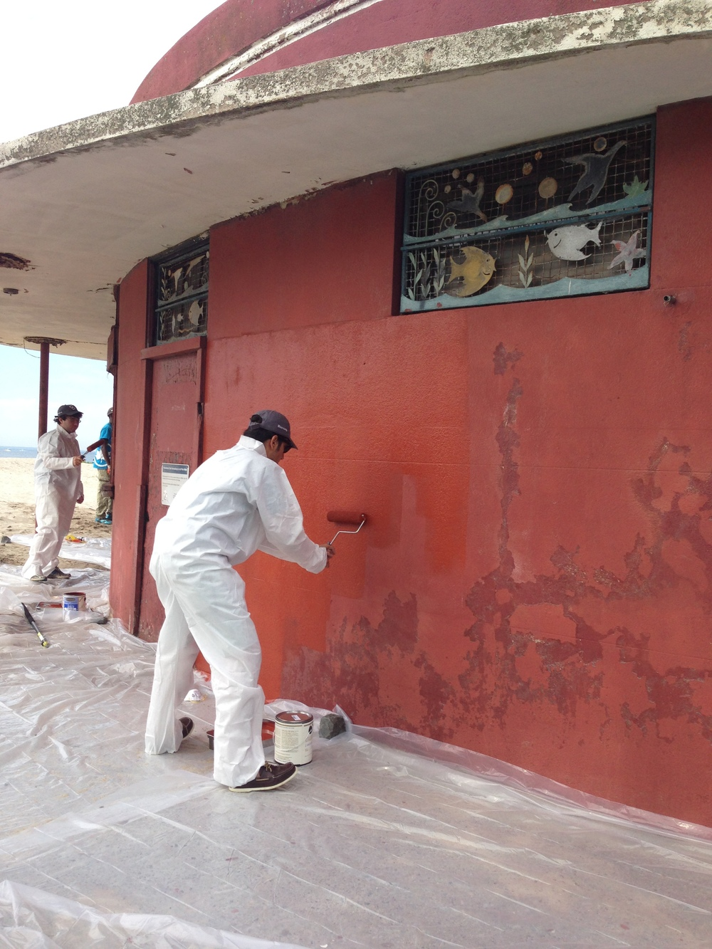 Volunteers coat the Plumb Beach Roundhouse with fresh paint.
