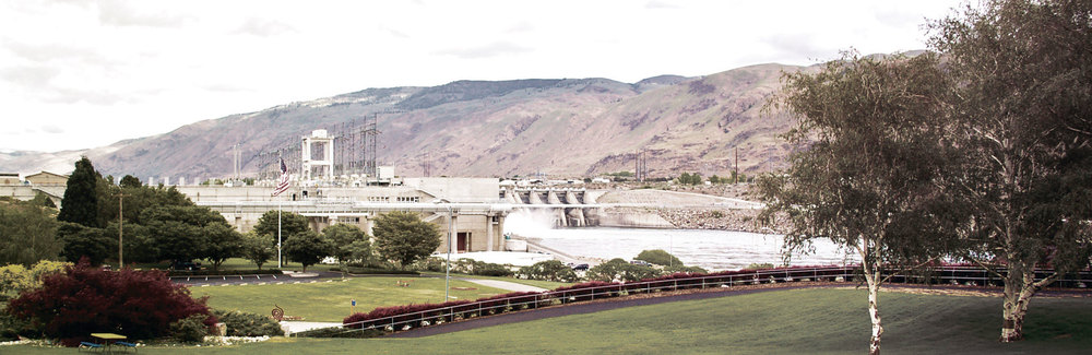 Rocky Reach Dam spans the Columbia River upstream from Wenatchee, powering homes and industry, and providing irrigation to the dry surrounding land for fertile crops. Badger Mountain, the highest point in Douglas County, graces the horizon behind.