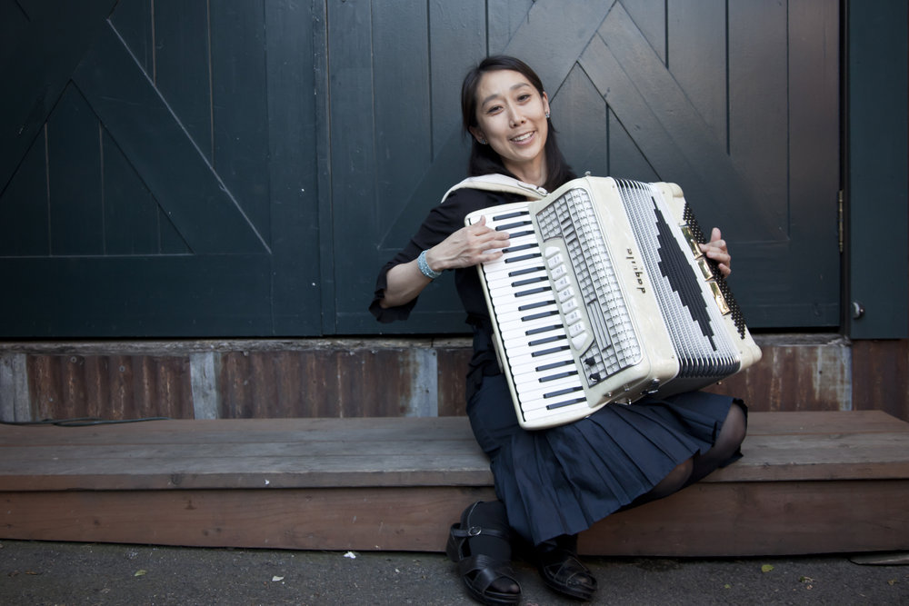 A coincidental collision of occurrences brought the accordion to Maggie Kim one summer many years ago: A mysterious large and clunky suitcase containing a musty accordion was placed next to her desk by a workmate; A dear childhood friend had been smitten by the accordion and invited her to visit and attend Cotati Accordion Festival; A newfound thrill for listening to the recordings of guitarist Django Reinhardt and other manouche jazz greats had opened an awareness of the musical history of that time in France.  At Cotati festival, Maggie was wandering through the merch booths and found a set of French music books in a bin. And as she curiously perused them, a realization dawned that the books were treasure! They were a collection of hundreds of waltzes written by the accordionists who played for the flourishing bal-musette dance halls of early 20th century France. These accordionists were accompanied by manouche banjo players and guitarists, including Django himself. And just as American jazz and swing was catching fire with those guitarists in the 1920's and 30's, some of the accordionists joined the club and began to swing and improvise as well.  These valse musettes continue to fascinate and delight Maggie. Their amazing confluence of classical technique, manouche bravado with eastern influence, sweet and catchy American jazz and swing elements, romantic French charm, and folk dance groove provide a limitless supply of awe, inspiration and study.  Maggie's favorite French accordionists are Gus Viseur, Jo Privat, Tony Murena, Michel Macias, Daniel Colin, Jean-Claude Laudat, Serge Desaunay. She also loves Edith Piaf, and Yann Tiersen's music for the film Amelie. She is thrilled to play this music with the perfect ambience, delicious bites, and kind folks found at Luc.
